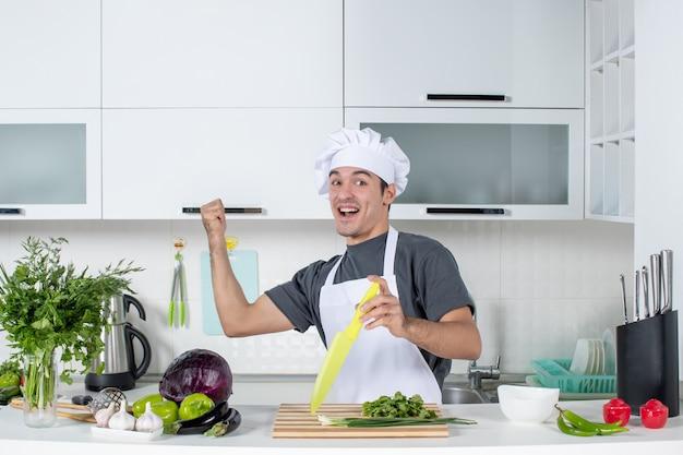 Vooraanzicht zeer gelukkige jonge kok in uniform wijzend op kast