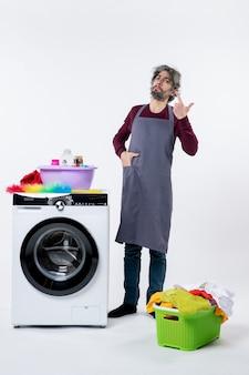 Vooraanzicht zelfverzekerde huishoudster man hand in zak staande in de buurt van witte wasmachine op witte achtergrond