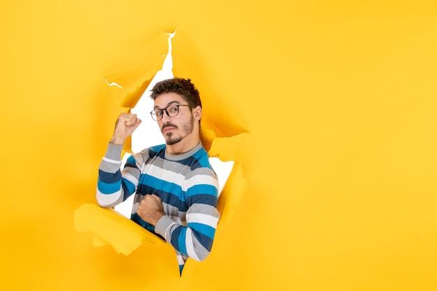 Vooraanzicht zelfverzekerde jonge man die door een gat in een papieren gele muur gluurt