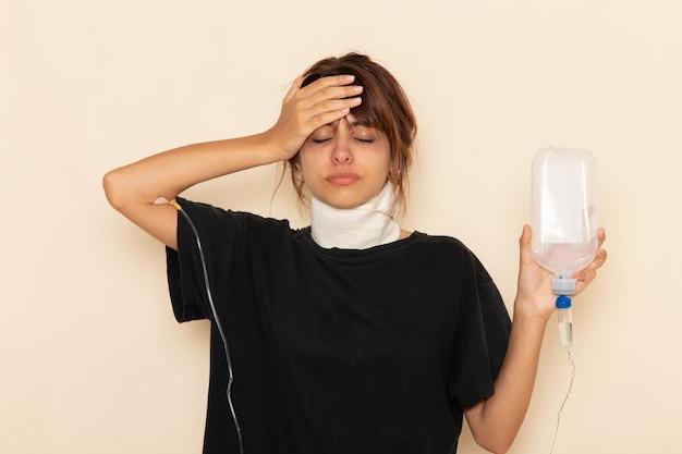 Vooraanzicht zieke jonge vrouw die zich erg ziek voelt en druppelaar op wit oppervlak gebruikt