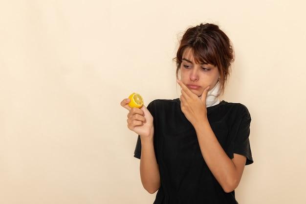 Vooraanzicht zieke jonge vrouw die zich ziek voelt en citroen vasthoudt die op een wit oppervlak denkt