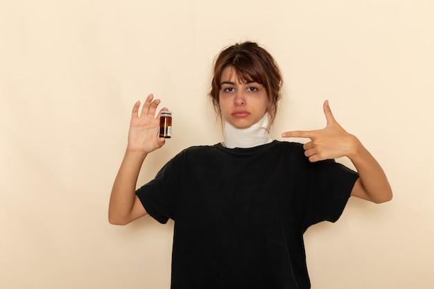 Vooraanzicht zieke jonge vrouw die zich ziek voelt en pillen op een witte ondergrond houdt