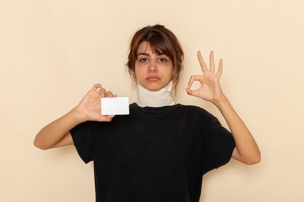 Vooraanzicht zieke jonge vrouw die zich ziek voelt met een witte kaart op een licht wit oppervlak
