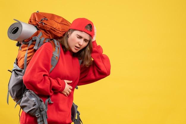 Vooraanzicht zieke reizigersvrouw in rode rugzak die haar maag en hoofd houdt
