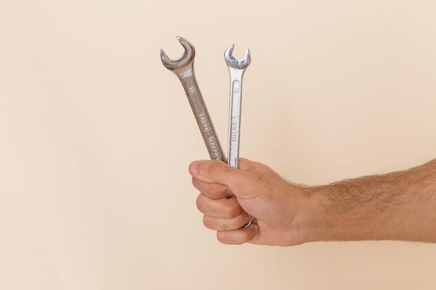 Vooraanzicht zilveren gereedschap vastgehouden door mannetje op licht bureau instrument gereedschap mannetje