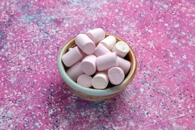 Vooraanzicht zoete heerlijke marshmallows weinig gevormd in ronde pot op roze bureau.