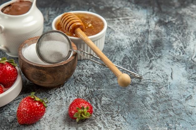 Vooraanzicht zoete honing met aardbeien op donkere oppervlakte zoete honing suikerbij