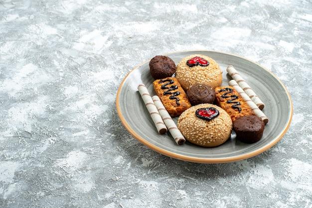 Vooraanzicht zoete koekjes binnen plaat op lichte witte ruimte