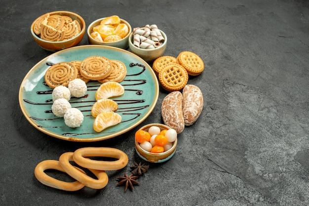 Vooraanzicht zoete koekjes met koekjes en suikergoed op het grijze zoete koekje van het lijstkoekje