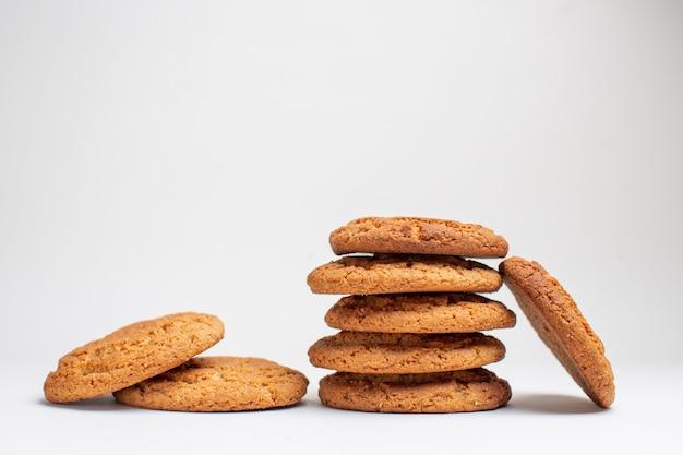 Vooraanzicht zoete koekjes op witte bureaukoekjes suiker dessert thee fotocake