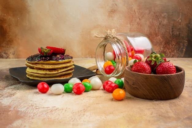 Vooraanzicht zoete pannenkoeken met kleurrijke snoepjes op licht bureau