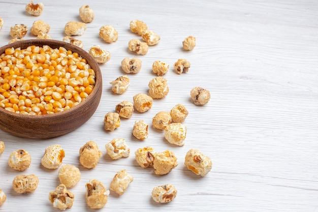 Vooraanzicht zoete popcorn met gele rauwe likdoorns op lichte ondergrond