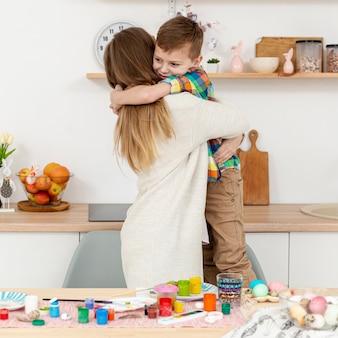 Vooraanzicht zoon knuffelen zijn moeder