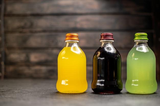 Vooraanzicht zwart geel en groen sap in flessen