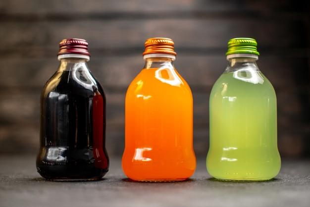 Vooraanzicht zwart sinaasappel en groen sap in flessen