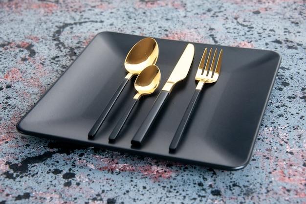 Vooraanzicht zwarte plaat met gouden vorklepels en mes op lichte achtergrond