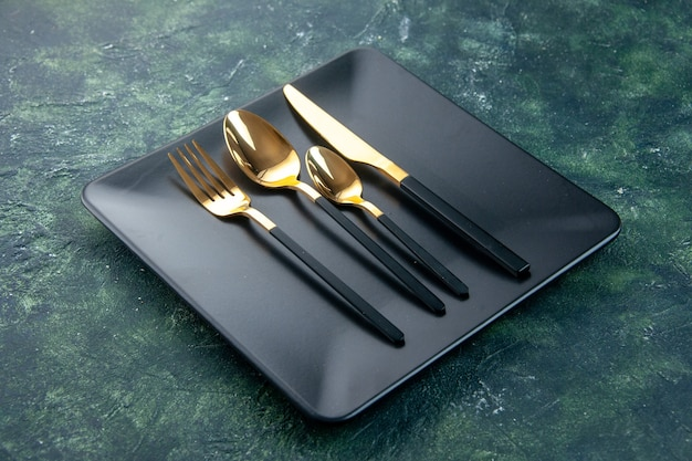 Vooraanzicht zwarte platen met gouden lepels mes en vork op donkere achtergrond
