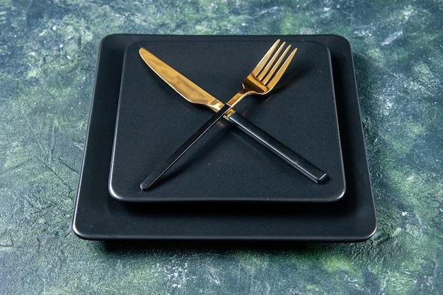 Vooraanzicht zwarte platen met gouden vork en mes gekruist op donkere achtergrond
