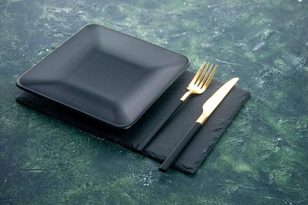Vooraanzicht zwarte vierkante plaat met gouden vork en mes op donkere achtergrond
