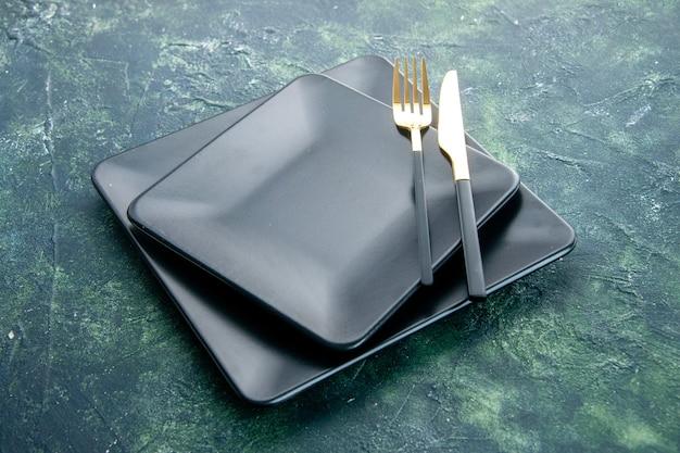 Vooraanzicht zwarte vierkante platen met gouden vork en mes op donkerblauwe achtergrond