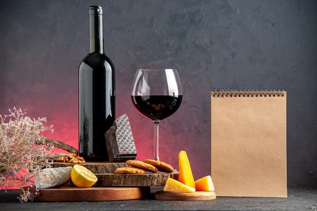 Vooraanzicht zwarte wijnfles rode wijn in glaskaas gesneden citroenstukjes donkere chocoladekoekjes op houten planken notitieboekje op rode tafel