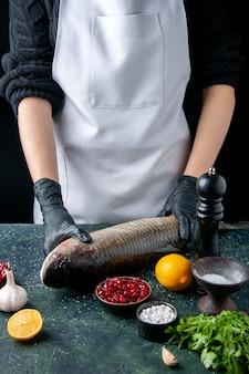 Vooraanzichtchef-kok in schort die rauwe vis op snijplank zet pepermolen granaatappelzaden in kom op tafel