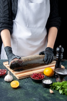Vooraanzichtchef-kok met zwarte handschoenen die rauwe vis op de snijplank zet, pepermolen, granaatappelzaden in kom op tafel
