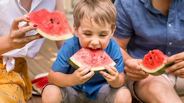 Vooraanzichtfamilie die samen watermeloen eet