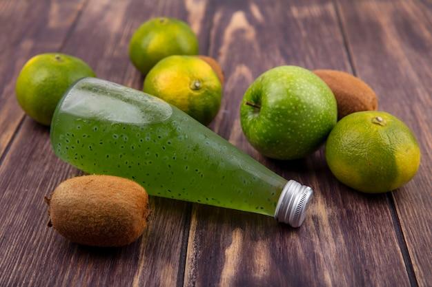 Vooraanzichtfles met sap met mandarijnenkiwi en appel op houten muur