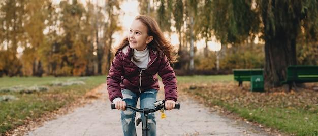 Vooraanzichtfoto van een kaukasisch meisje dat de fiets in het park berijdt terwijl zij haar ouders bekijkt