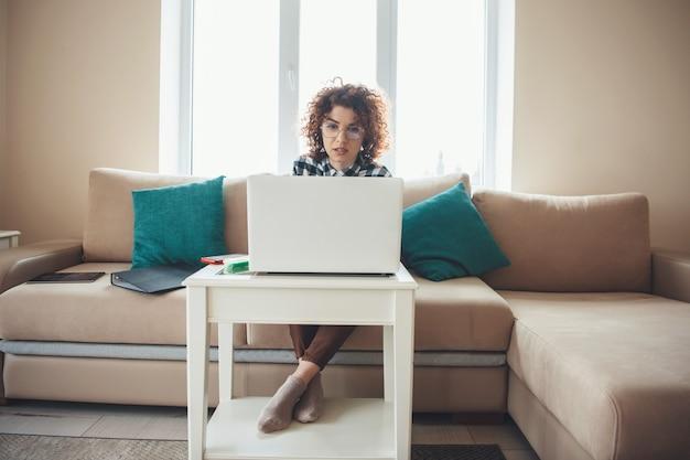 Vooraanzichtfoto van een vrouw met krullend haar met een online bijeenkomst op de laptop zittend op de bank