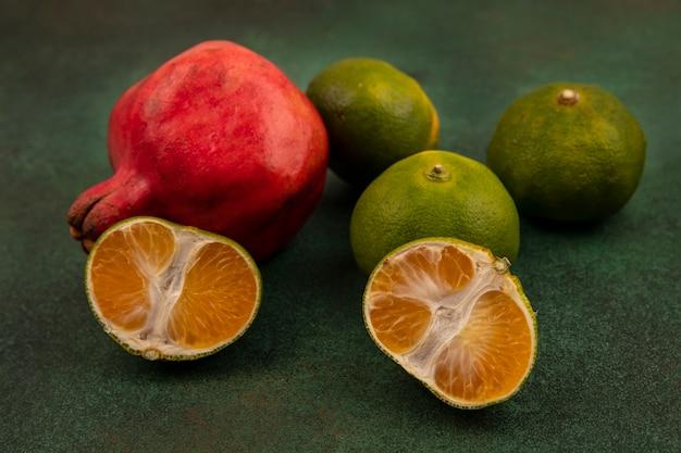 Vooraanzichtgranaatappel met mandarijnen op een groene muur