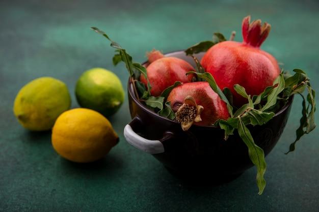 Vooraanzichtgranaatappels met takken in een pan met citroen en limoenen op een groene achtergrond