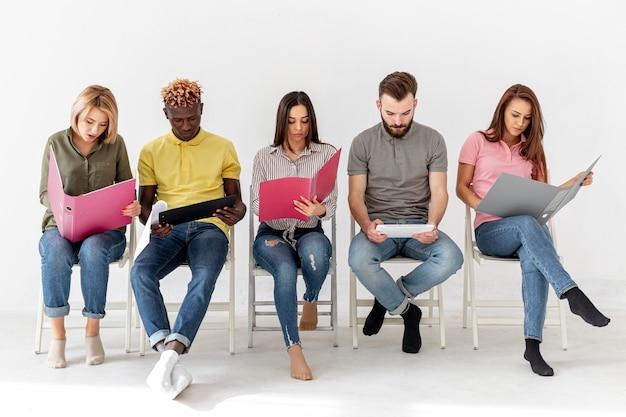 Vooraanzichtgroep vrienden die op stoelen zitten