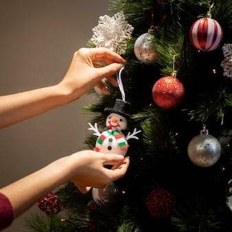 Vooraanzichthanden die bollen op kerstmisboom zetten