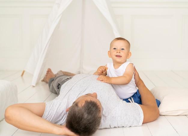 Vooraanzichtjong geitje het spelen met vader in tent
