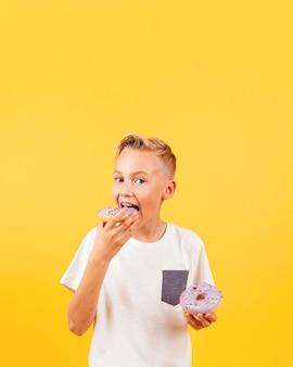 Vooraanzichtjongen die doughnuts eet