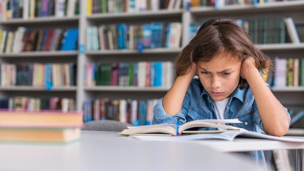 Vooraanzichtjongen die hard nadenkt over het oplossen van zijn huiswerk met exemplaarruimte