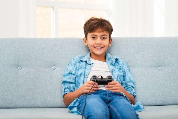 Vooraanzichtjongen die met joystick speelt