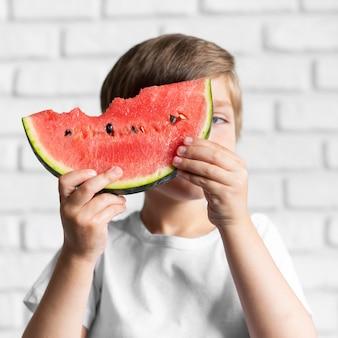 Vooraanzichtjongen die watermeloen eet