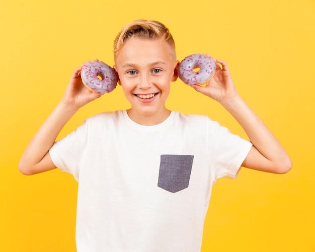 Vooraanzichtjongen met donuts bij zijn oren