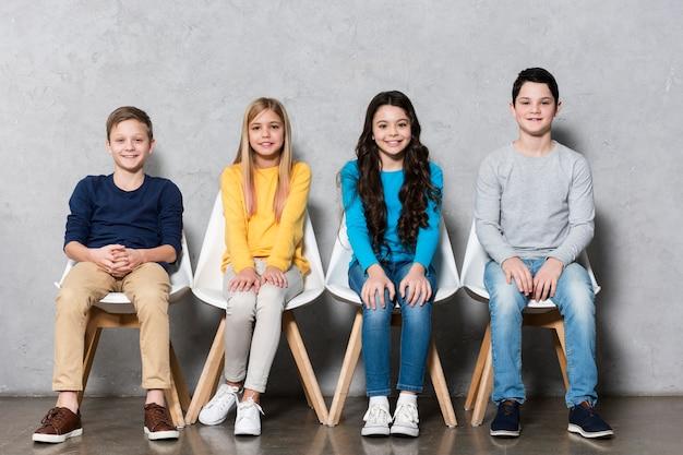 Vooraanzichtkinderen die op stoelen zitten