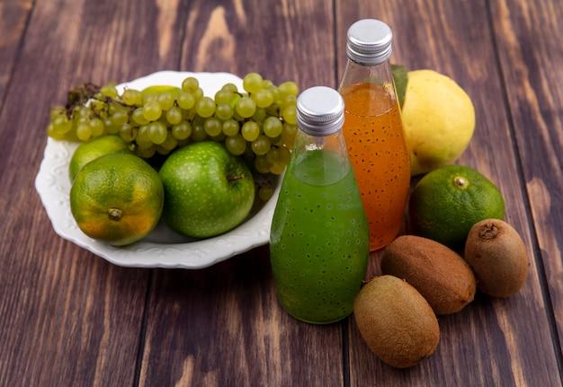 Vooraanzichtkiwi met de druiven van mandarijnenappelen en sap in flessen op houten muur