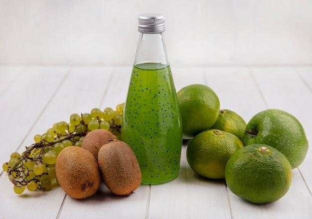 Vooraanzichtkiwi met een fles sapdruiven en mandarijnen op een witte muur