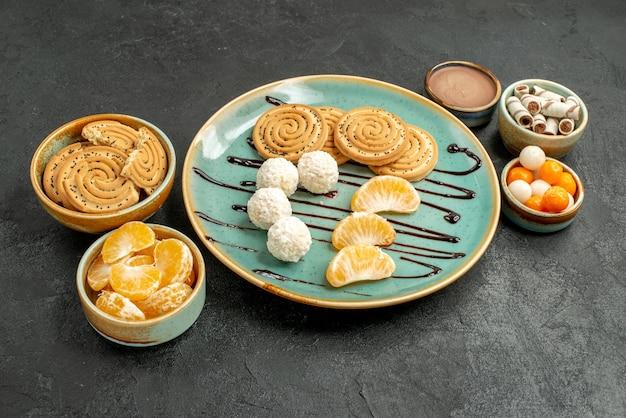 Vooraanzichtkoekjes en suikergoed met mandarijnen op het grijze koekje van het lijst zoete koekje
