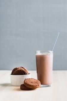 Vooraanzichtkoekjes met chocolademelk in glas met stro