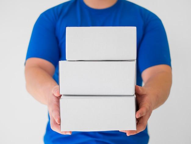 Vooraanzichtkoerier die witte dozen houdt