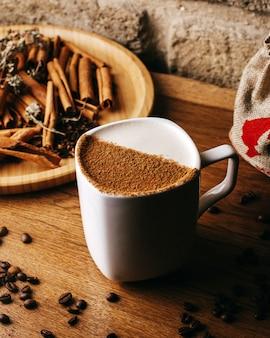 Vooraanzichtkoffie samen met kaneel en koffiezaden op de bruine vloer