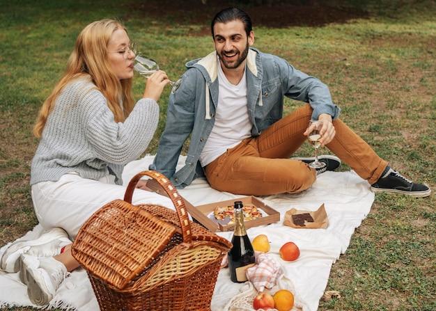 Vooraanzichtman en vrouw die een picknick in het park hebben
