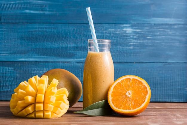 Vooraanzichtmango en oranje smoothie in fles